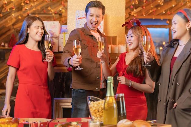 Partij van aziatische vrienden die van kerstdrankjes genieten en close-up glazen van rammelende vieren?