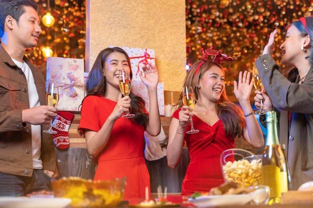 Partij van aziatische vrouwelijke en mannelijke vieren van geluk vrienden kerstavond vieren diner