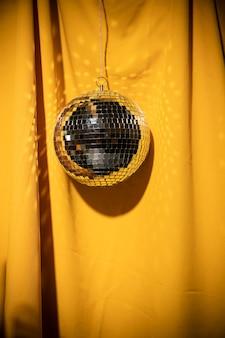 Partij van de lage hoek de zilveren bol op geel gordijn