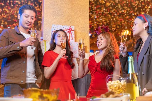 Partij van mooie aziatische vriend, vrouw en man die geluk viert, kerstfeest viert diner