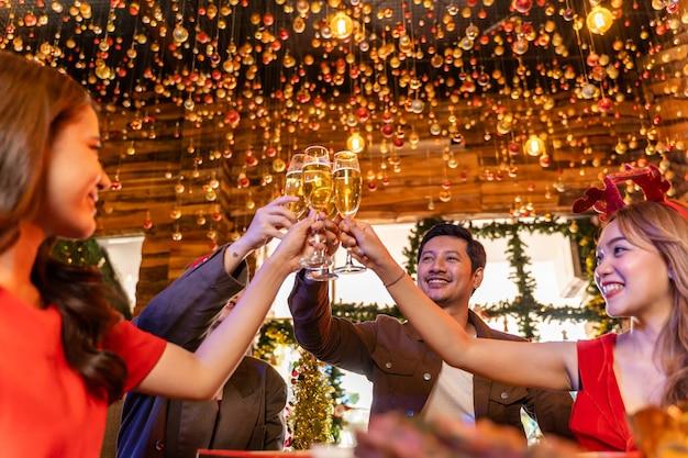 Partij van mooie aziatische vriend, vrouw en man die geluksvrienden vieren op kerstavond