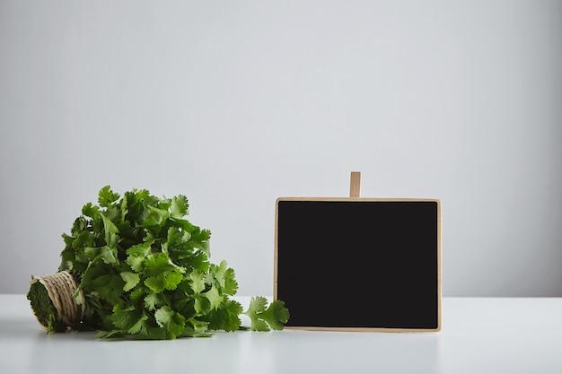 Partij verse groene peterselie koriander gebonden met ambachtelijke touw in de buurt van krijtbord prijskaartje geïsoleerd op een witte tafel en eenvoudige achtergrond. klaar voor verkoop. oogst markt concept