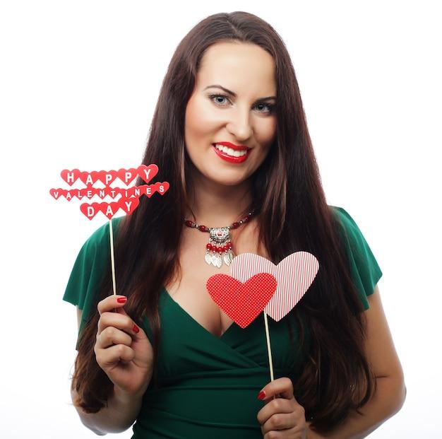 Partijconcept: jonge mooie vrouw die groene kleding draagt die document harten houdt