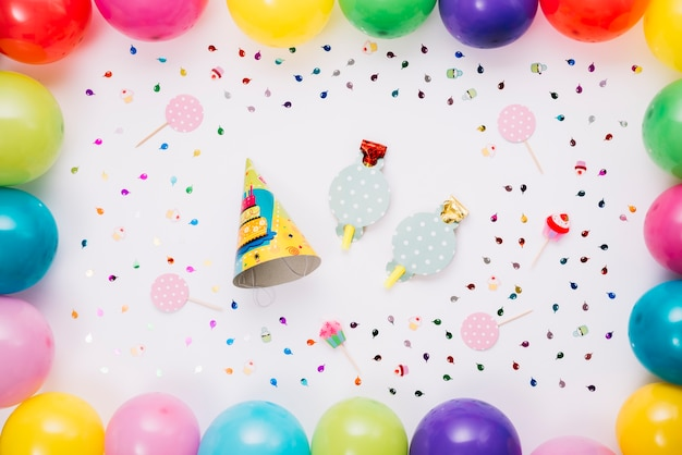 Partijhoed en hoornblazer met kleurrijke die ballons en confettien wordt op witte achtergrond worden geïsoleerd verfraaid die