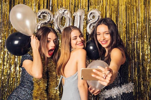 Partijmeisjes die zelfie op nieuwjaarspartij nemen