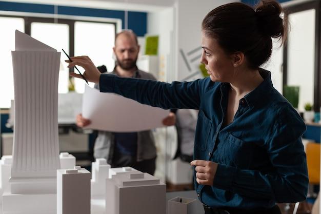 Partners van architectenbureaus kijken naar blauwdrukken en plannen