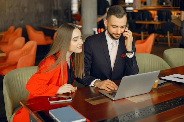 Partners zitten aan de tafel en werken in een café