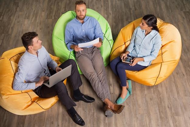 Partners zittend op zitzakken en working