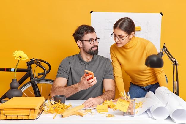 Partnerschap en communicatieconcept. geschoolde vrouw en man kantoormedewerkers werken aan het ontwerpen van grafische pose op rommelige desktop met blauwdrukken genereren creatieve ideeën voor toekomstig architectonisch project