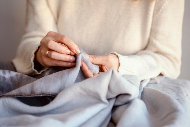 Pas vrouw aan die naald en draad gebruikt om te naaien