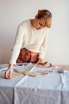 Pas vrouw aan met behulp van liniaal om de stof te meten