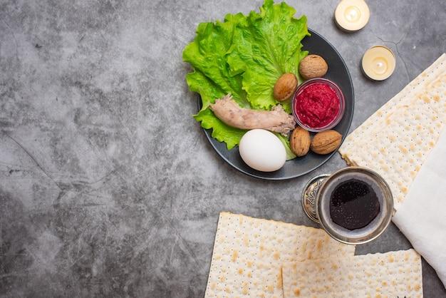 Pascha achtergrond met wijn, matza en seder plaat op grijs.