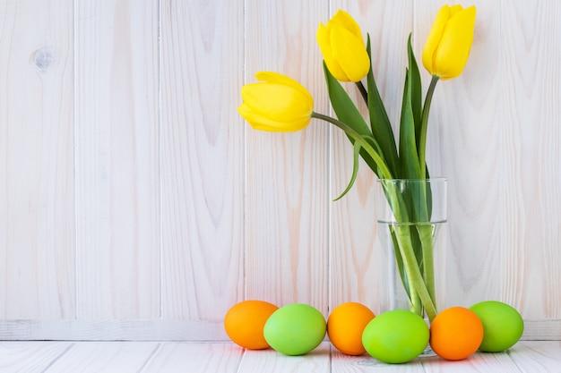 Paschal wenskaart, mockup met ruimte voor tekst. feestelijk pasen-kader met kleurrijke eieren en boeket van gele tulpen op lichte houten achtergrond.