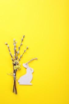 Pasen achtergrond. boeket van wilgen en hout konijn op een geel papier