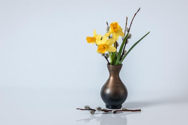 Pasen achtergrond. de lenteachtergrond met gele gele narcissen en wilgentakken in vaas.