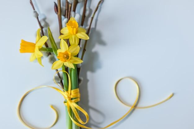 Pasen achtergrond. de lenteachtergrond met gele gele narcissen en wilgentakken
