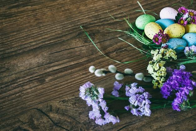 Pasen achtergrond. heldere kleurrijke eieren in nest met lentebloemen over houten donkere achtergrond