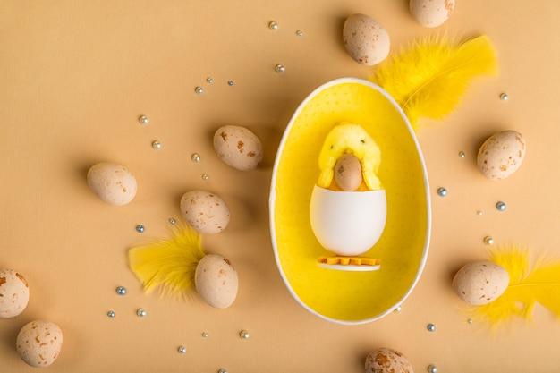 Pasen-achtergrond met beige marsepeinpaaseieren, kuiken en de lentebloemen
