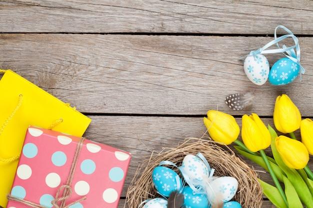 Pasen-achtergrond met blauwe en witte eieren in nest, gele tulpen en giftdoos