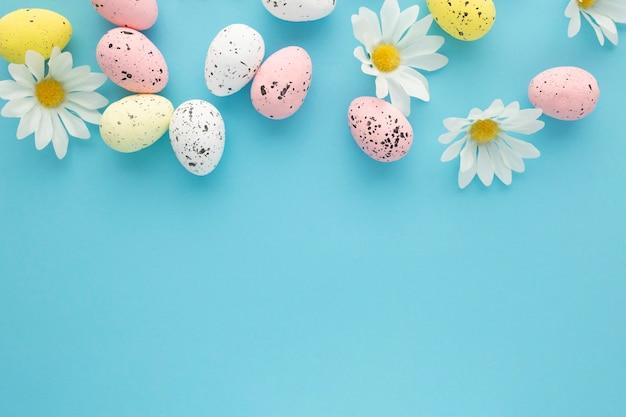 Pasen-achtergrond met eieren en madeliefjes op een blauwe achtergrond met exemplaarruimte