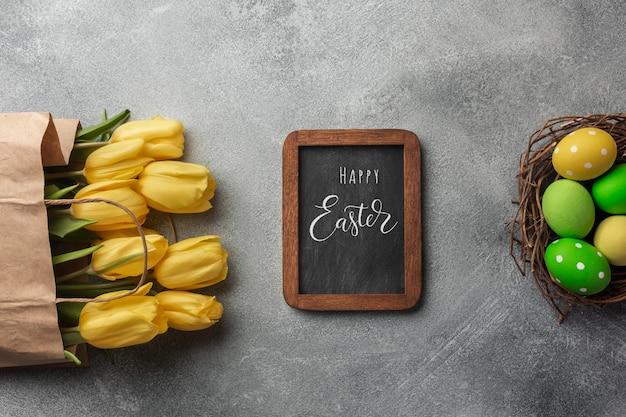 Pasen-achtergrond met kleurrijke eieren en gele tulpen op grijze steen. bovenaanzicht met kopie ruimte.