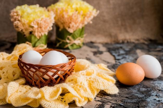 Pasen-achtergrond met kleurrijke eieren en gele tulpen over wit hout.
