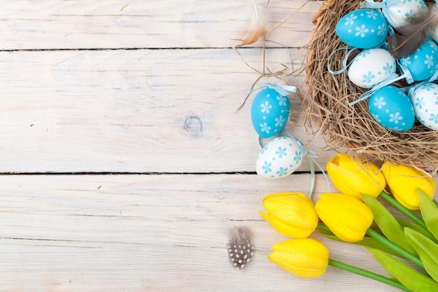Pasen-achtergrond met kleurrijke eieren en gele tulpen