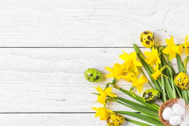 Pasen-achtergrond met paaseieren en de bloemen van de lentenarcissen op witte houten achtergrond. plat lag. bovenaanzicht