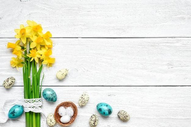 Pasen-achtergrond met paaseieren en de lentebloemen op witte houten lijst