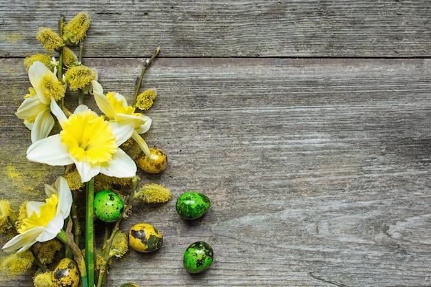 Pasen-achtergrond met paaseieren en de lentegele narcis en willo