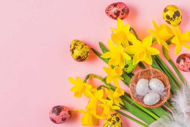 Pasen-achtergrond met paaseieren en de narcissenbloemen van de lente op pastelkleur roze achtergrond. plat lag. bovenaanzicht