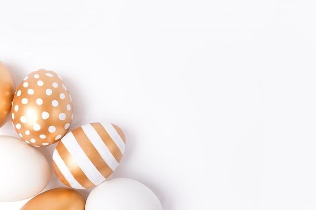 Pasen-achtergrond of pasen-concept. gouden verfraaide eieren van pasen die op witte achtergrond worden geïsoleerd