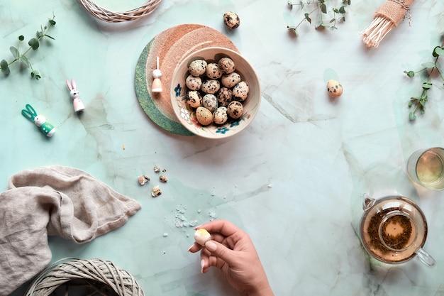 Pasen-achtergrond op muntgroene marmeren lijst. kwartel paaseieren en natuurlijke lentedecoraties en eucalyptustakjes. groene thee in glazen theepot.