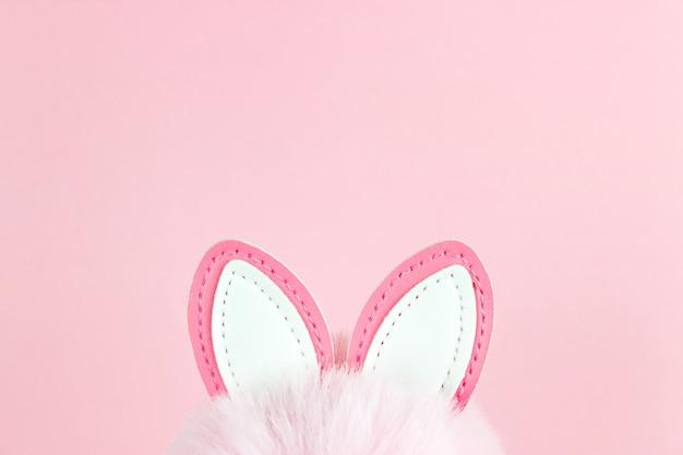 Pasen achtergrond. oren van een paashaas op roze achtergrond. lente vakantie viering foto ontwerpsjabloon.