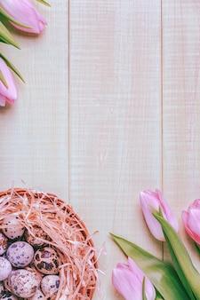 Pasen achtergrond roze tulpen op houten tafel kwartel eieren nest