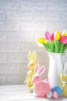 Pasen achtergrond. vaas met een boeket tulpenbloemen, paaseieren en konijntjesdecor. op witte houten keukentafel achtergrond kopie ruimte
