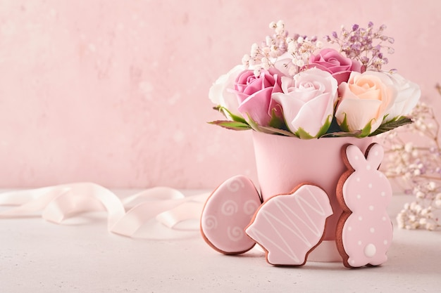 Pasen-achtergronddecoratie met mooi boeket roze rozenbloemen in vaas, paaseieren, konijntje en kuiken op roze achtergrondlijst. pasen concept met kopie ruimte.