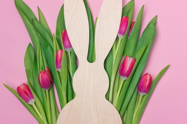 Pasen-banner met houten konijntjescijfer en purpere verse tulpen. ruimte voor tekst kopiëren