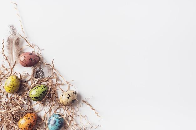 Pasen beschilderde eieren en hooi op een witte achtergrond, plat plat, bovenaanzicht, kopieer ruimte. minimalistische pasen-achtergrond. fijne paasgroeten.