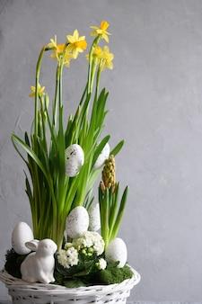 Pasen-bloemsamenstelling met bloesemnarcissus en hyacintbloemen en witte eieren in bloempot. feestelijke wenskaart.