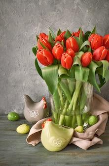 Pasen: bos rode tulpen, lentedecoratie op grijze rustiek