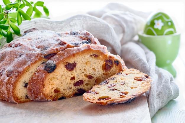 Pasen-brood, close-up op traditioneel fruitig brood op rustiek hout met verse bladeren en geschilderd ei