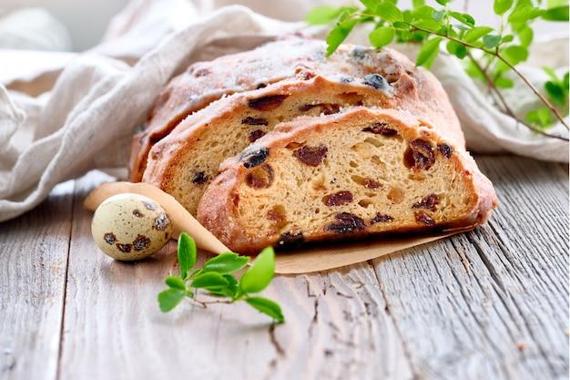 Pasen-brood, close-up op traditioneel fruitig brood op rustiek hout met verse bladeren en kwartelsei