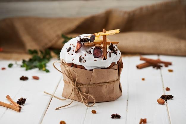 Pasen-cake door droge vruchten en pijpjes kaneel op witte houten achtergrond, traditionele kulich, paska wordt verfraaid klaar voor viering wordt verfraaid die