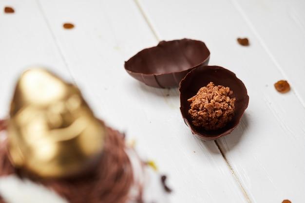 Pasen-cake door gouden chocolade-ei wordt verfraaid op witte houten achtergrond, traditionele kulich, paska klaar voor viering die