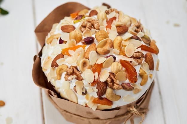 Pasen-cake door noten en droge vruchten op witte houten achtergrond, traditionele kulich, paska klaar voor viering wordt verfraaid die
