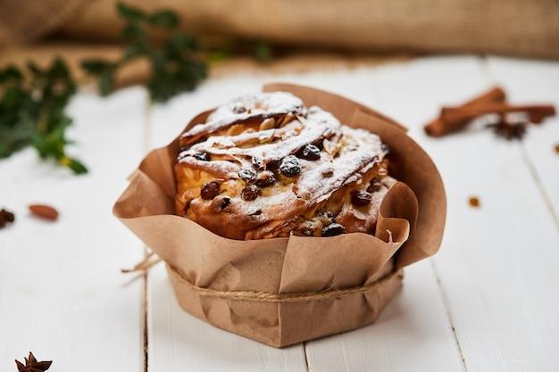 Pasen-cake door rozijnen en suikerglazuursuiker wordt verfraaid op witte houten achtergrond, traditionele kulich, paska klaar voor viering die