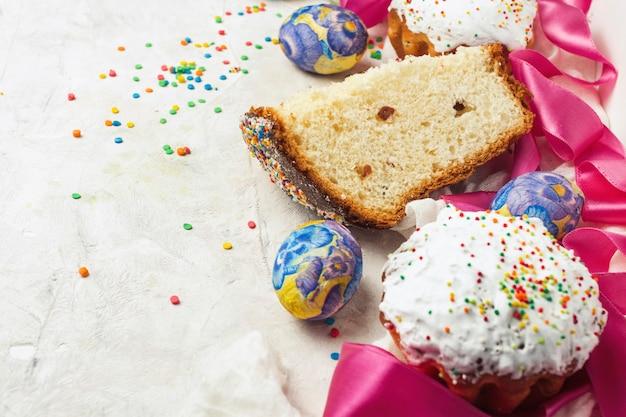 Pasen-cake en één stuk, roze lint, kleurrijke snoepjes op een lichte achtergrond.