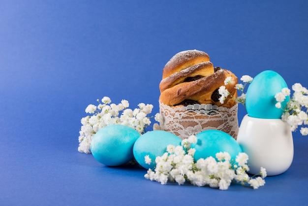Pasen-cake en geschilderde blauwe eieren op een trendy blauwe achtergrond.