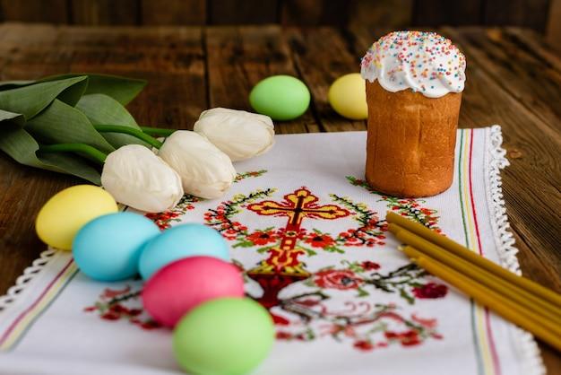 Pasen-cake en kleurrijke eieren op een houten lijst.